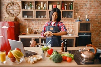 Black woman in apron cooking healthy breakfast