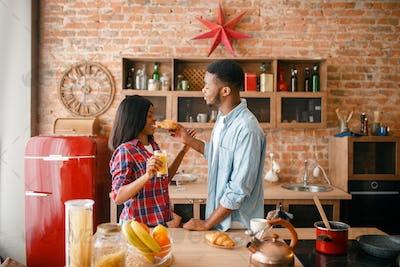 Playful black couple having fun on the kitchen