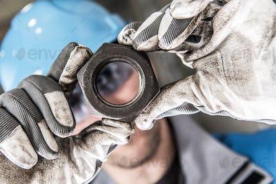 Metal Nut in Worker Hands