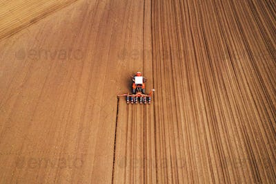 Drone photography of tractor with seeder working in field