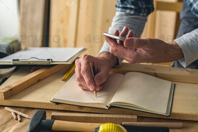Carpenter is writing project notes while using smartphone