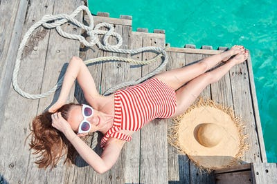 Woman in one-piece swimsuit on wooden jetty