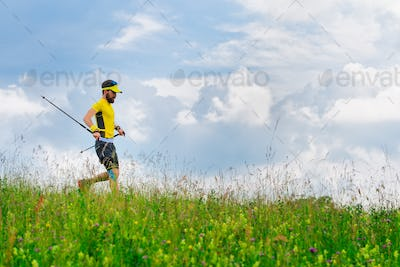 Young man runs down in the green grass