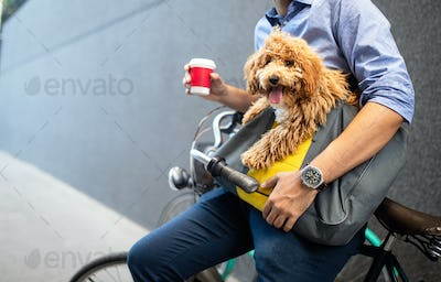 Young man drinking coffee while sitting on his bicycle with dog outdoors