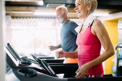 Happy senior people running together on treadmills in gym