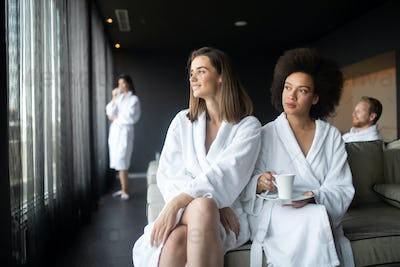 Attractive happy young women drinking coffee at spa center