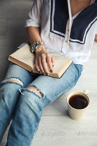 Young modern girl in torn jeans reading a book with a big cup of coffee. Fashion, lifestyle