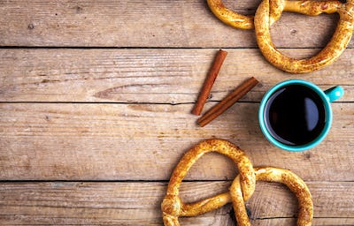 Delicious Breakfast, a pretzel with coffee on wooden background. The food, the drinks
