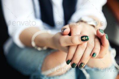 Stylish girl sitting in torn jeans and modern green nail Polish