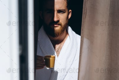 Male in white bathrobe with coffee mug in hand