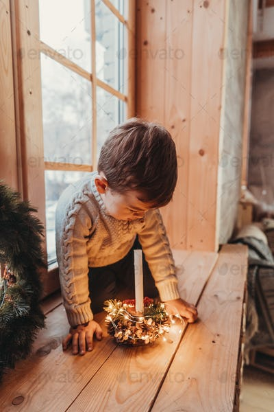 Little boy playing with a candle. Child is sitting on windowsill