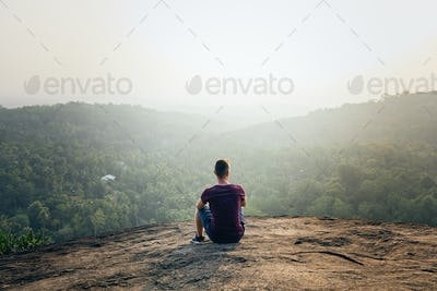Man resting on top of rock