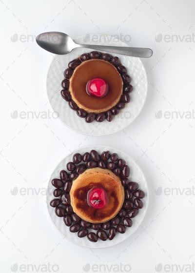 aerial view of two egg custards, on plate, with chocolate covered peanuts isolated on white