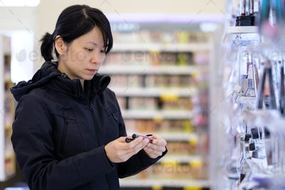 Beautiful Asian woman choosing personal care product in supermarket