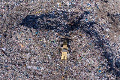 Aerial drone view of bulldozer working on landfill, trash dump