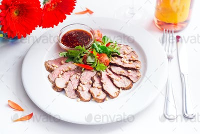 Tasty sliced roast duck breast with fresh vegetable salad and with cranberry sauce. Peking duck