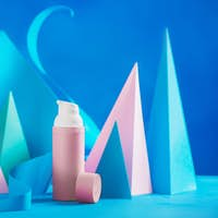 Cosmetics and skin care design with pink tubes and paper sculpture in pastel tones on a blue
