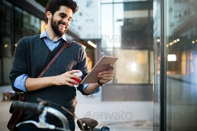 Portrait of young man holding tablet and coffee outdoor