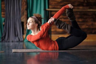 Woman practicing yoga, doing Dhanurasana exercise, Bow pose