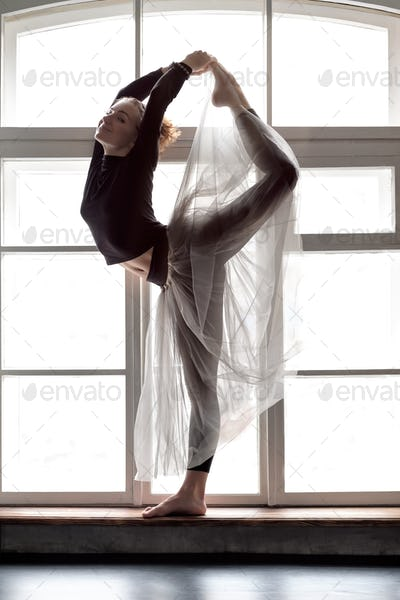 Woman practicing yoga, doing Natarajasana exercise, Lord of the Dance pose