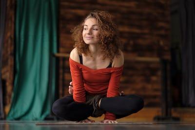 woman yoga instructor doing Cock Pose or Rooster, Kukkutasana asana