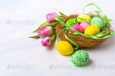 Easter nest with painted eggs and tulips, copy space