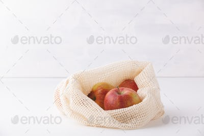 Red apples in reusable cotton bags. Copyspace