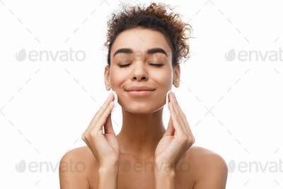 Young woman cleaning her face with cotton pads