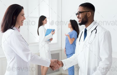 Doctor handshaking with african-american intern in clinic