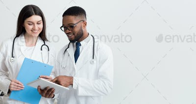 Doctor giving his colleague a piece of advice, light background