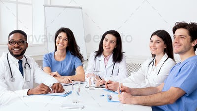 Young interns listening to professor in conference room