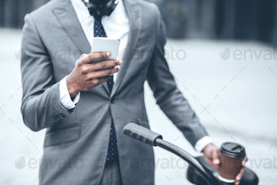 Businessman texting on phone leaning on the handlebars