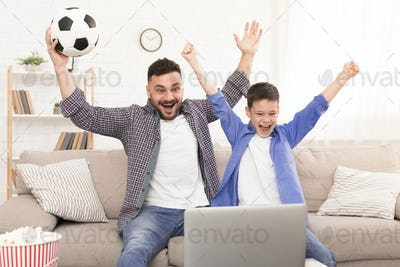 Excited father and son watching football on laptop