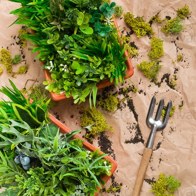 Gardening rake and artificial plants in pots on rumpled craft paper