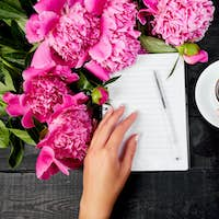Woman hand writing diary, or letter, note with cup of coffee