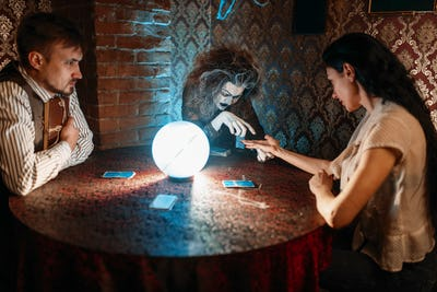 Foreteller guessing by hand over a crystal ball