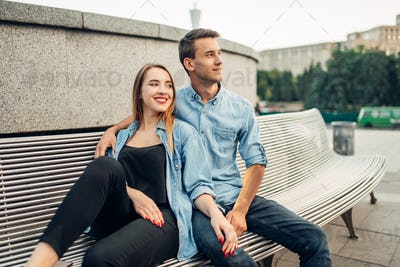 Couple sitting on the bench in summer city park