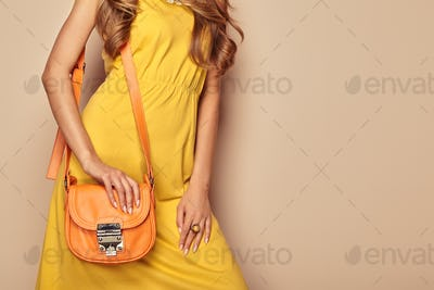 Blonde young woman in yellow spring summer dress