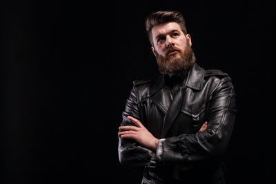 Attractive bearded man keeping his arms crossed over blac background