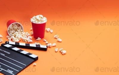 Clapperboard and pop corn on orange color background