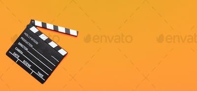 Movie clapperboard on orange color background, banner, top view
