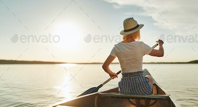 Young woman canoeing on a still lake in the summer
