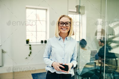 Smiling young businesswoman standing in a modern office