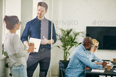 Diverse businesspeople talking and working together in an office