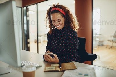 Laughing young businesswoman using a cellphone at her office desk