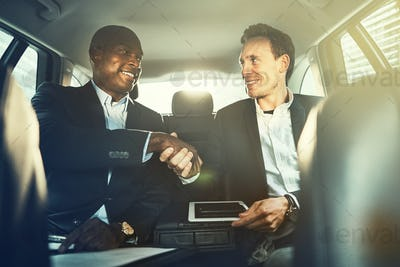 Businessmen shaking hands together in the backseat of a car