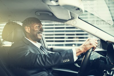 Smiling African businessman driving his car through the city streets