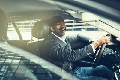 Smiling young African businessman driving in the city