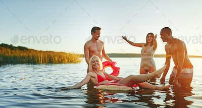 Smiling friends having fun together in a lake in summer