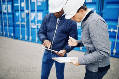 Engineers standing in a shipping yard comparing inventory lists